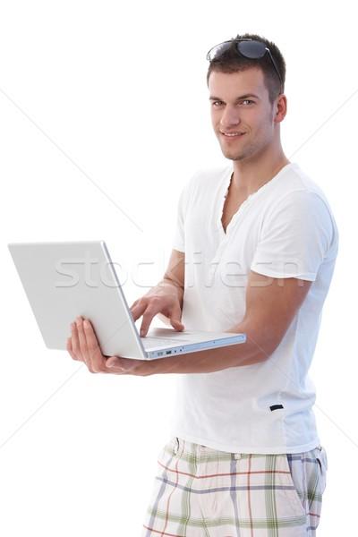 Young man using laptop smiling Stock photo © nyul
