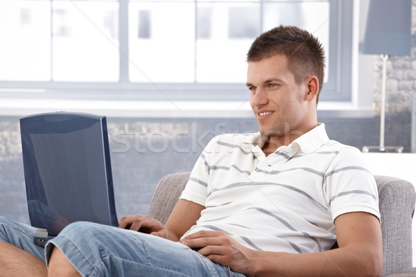 College student browsing internet at home smiling Stock photo © nyul