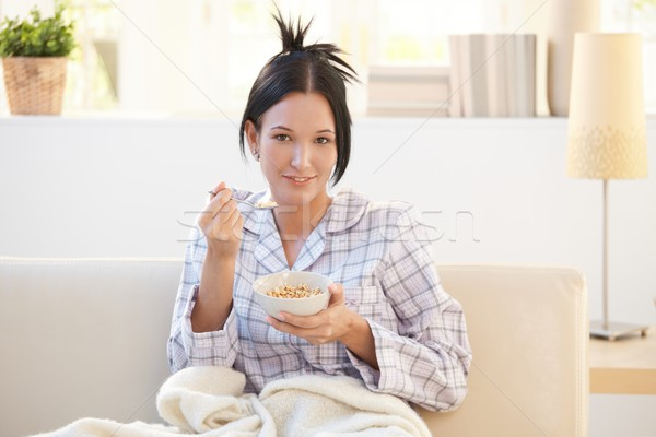 Girl in pyjama having cereal breakfast on couch Stock photo © nyul
