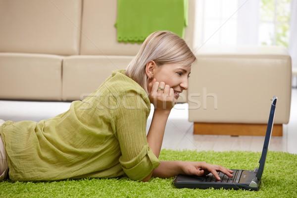 Stok fotoğraf: Gülümseyen · kadın · bilgisayar · ev · zemin · bakıyor · dizüstü · bilgisayar