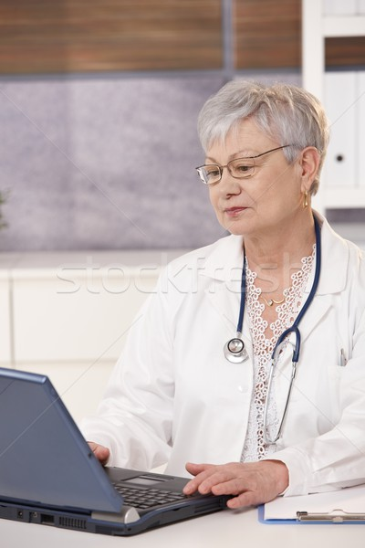 Stock photo: Senior doctor using laptop