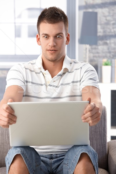 Young man staring at laptop screen horrified Stock photo © nyul