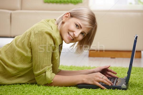 Stok fotoğraf: Gülümseyen · kadın · bilgisayar · ev · bakıyor · kamera · zemin
