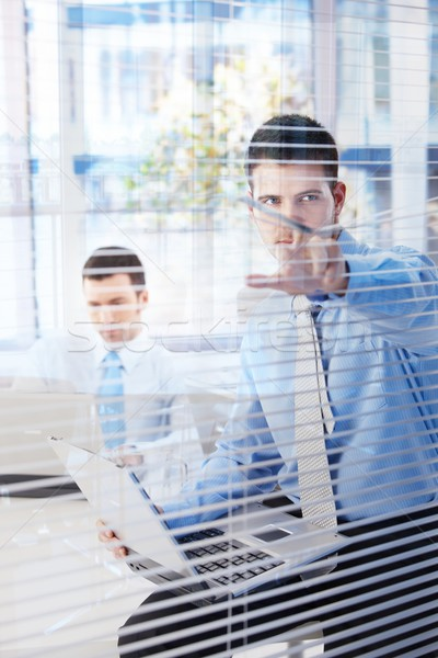 Young businessman peeping corridor through blind Stock photo © nyul
