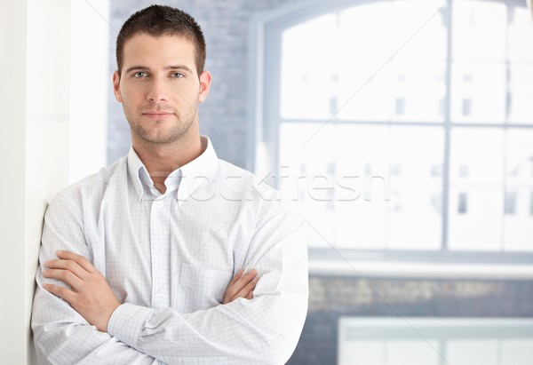 Goodlooking young man standing arms crossed Stock photo © nyul