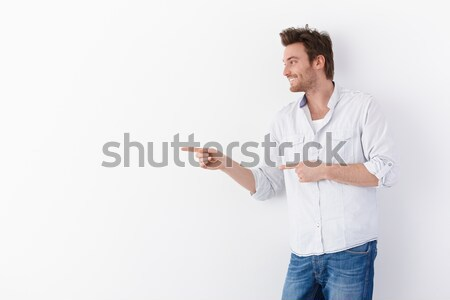 Moço indicação direito em pé branco sorridente Foto stock © nyul