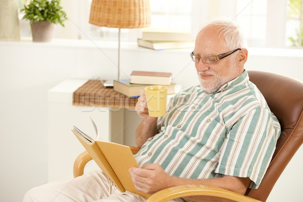 Stock photo: Smiling senior relaxing at home with book and tea