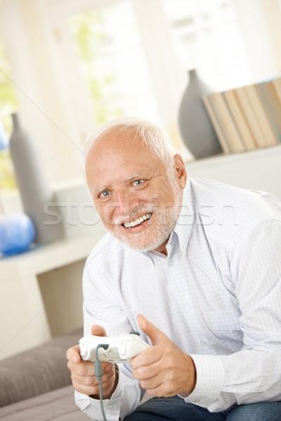 Senior man genieten computerspel lachend vergadering Stockfoto © nyul