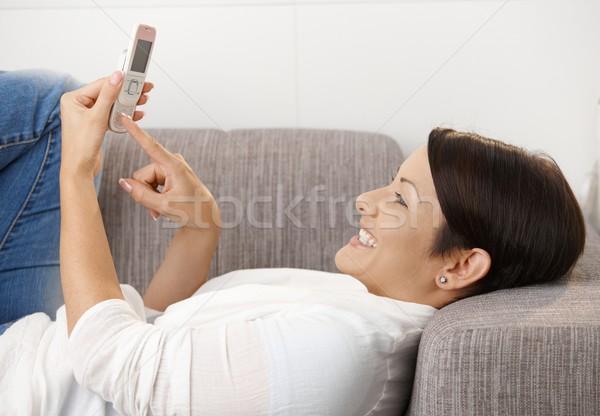 Smiling woman writing text message Stock photo © nyul