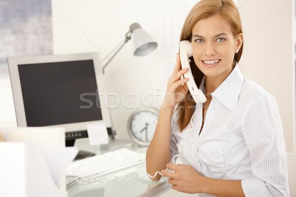 Happy office girl on landline phone call Stock photo © nyul