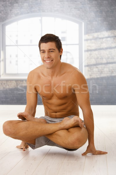 Stock photo: Smiling guy in lotus posture