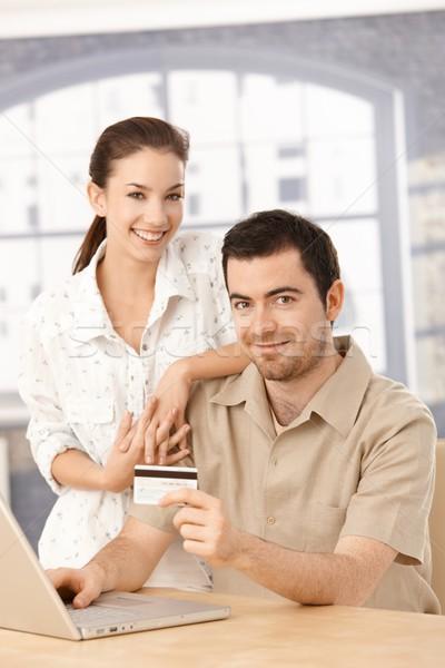 Happy couple enjoying online shopping smiling Stock photo © nyul