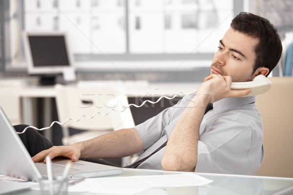 Young male sitting at desk talking on phone Stock photo © nyul