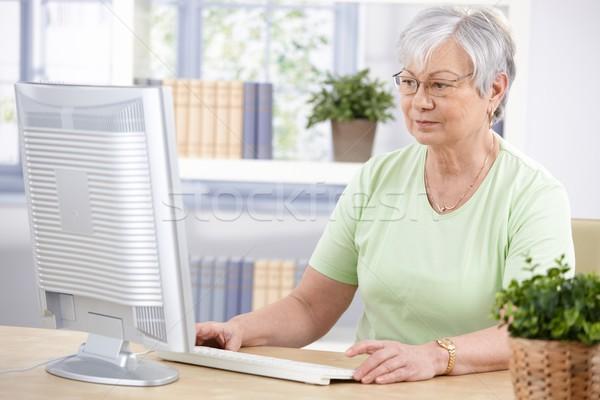 Senior woman using computer at home Stock photo © nyul