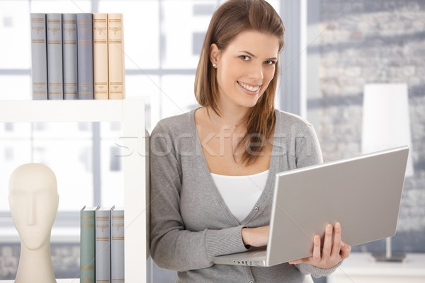 Happy woman at bookcase with computer Stock photo © nyul