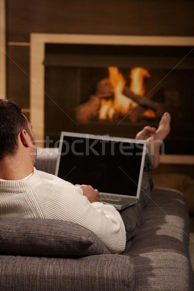 Stock fotó: Férfi · ül · kandalló · kanapé · otthon · laptopot · használ