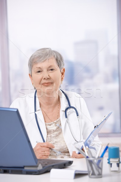 Stock photo: Senior doctor working at desk