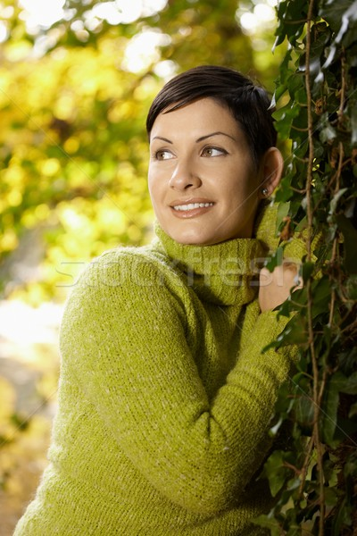 Portrait of young woman leaning to tree trunk Stock photo © nyul