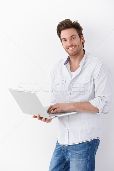 Handsome man with laptop smiling Stock photo © nyul
