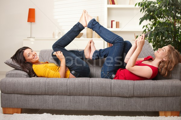 Stock photo: Smiling teens lying on couch