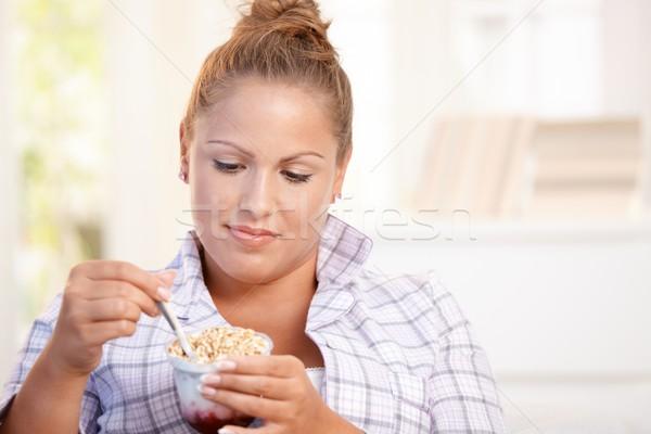 Pretty girl eating yoghurt at home dieting Stock photo © nyul