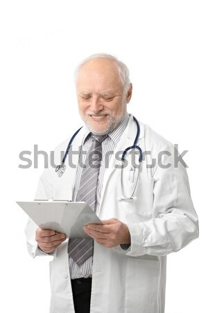 Stock photo: Senior doctor looking at papers smiling
