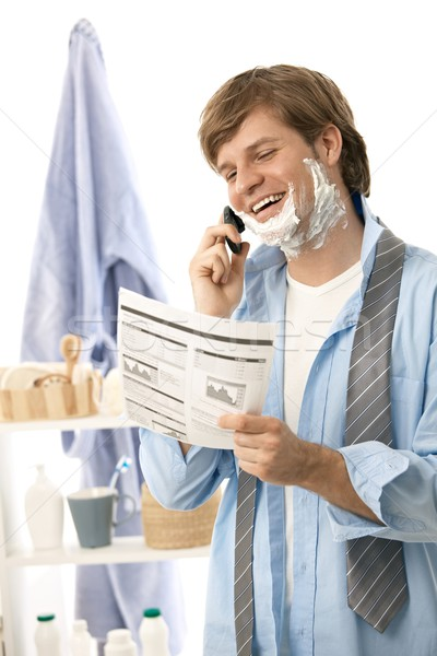 Man reviewing document while shaving Stock photo © nyul