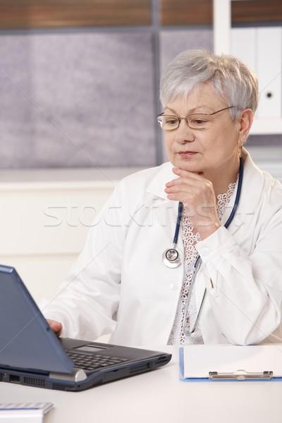 Stock photo: Senior doctor looking at computer