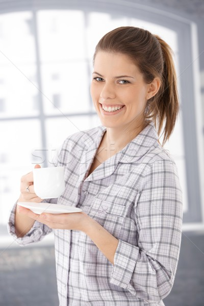 Happy woman in pyjama with coffee cup Stock photo © nyul