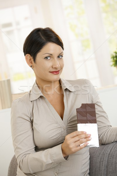 Guiltily looking woman eating chocolate Stock photo © nyul