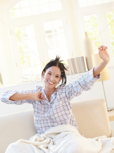 Happy attractive woman stretching in pyjama Stock photo © nyul