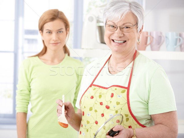 Cheerful senior mother cooking in kitchen Stock photo © nyul