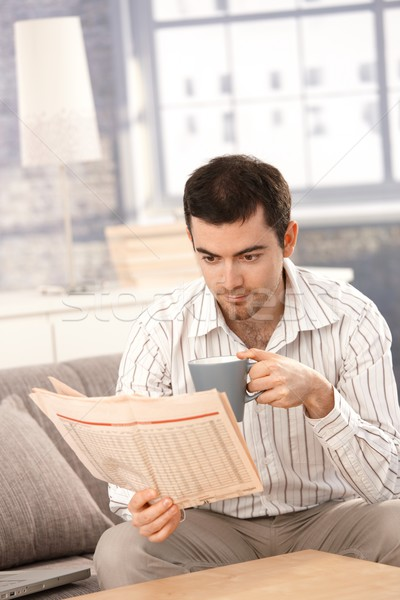Young man reading news drinking tea in the morning Stock photo © nyul