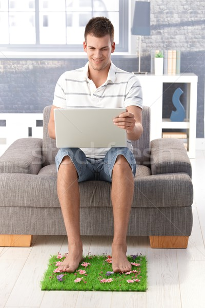 College student using laptop smiling at home Stock photo © nyul