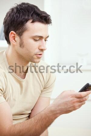 Fiatalember sms fiatal jóképű férfi mobiltelefon ház Stock fotó © nyul