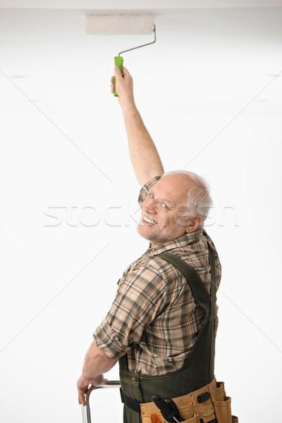 Elderly man painting the ceiling Stock photo © nyul