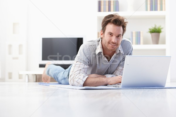 Handsome man laying on floor at home smiling Stock photo © nyul