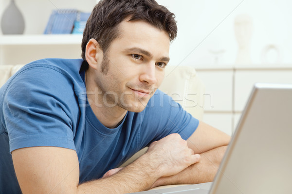 Stock photo: Young man using laptop at home