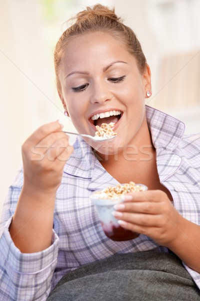 Pretty girl eating yoghurt at home dieting smiling Stock photo © nyul