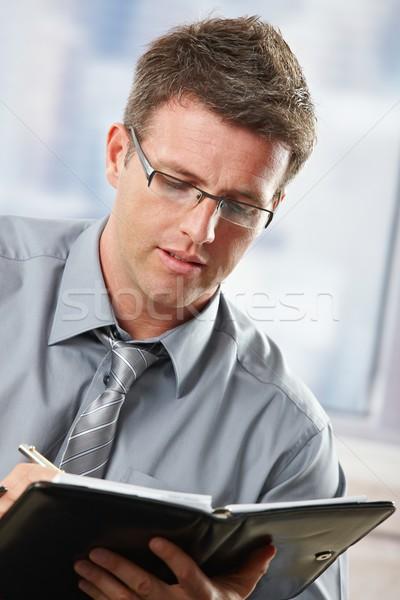 Businessman taking notes into organiser Stock photo © nyul