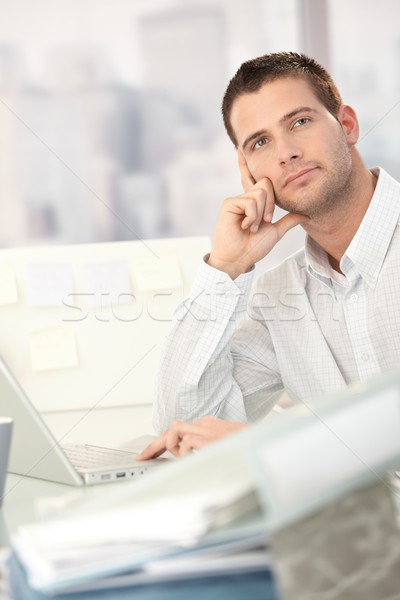 Stock photo: Daydreaming young man sitting at desk