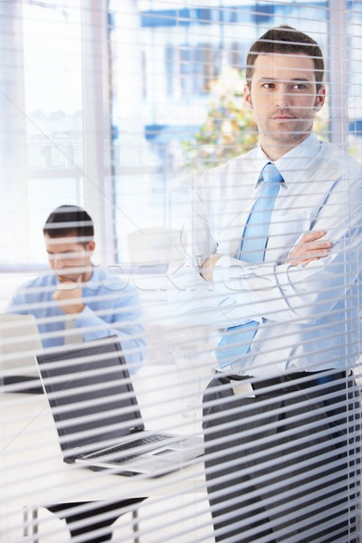 Stock photo: Young businessman looking through blind thinking