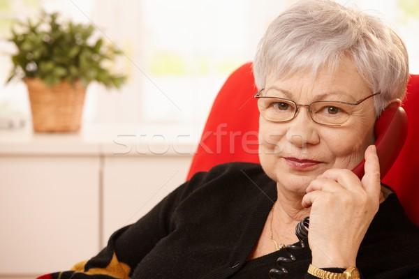 Senior woman with landline phone in hand Stock photo © nyul