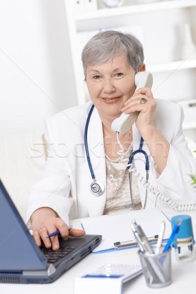 Foto stock: Senior · médico · falante · telefone · feminino · trabalhando