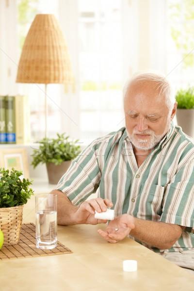 Senior man taking medication at home Stock photo © nyul