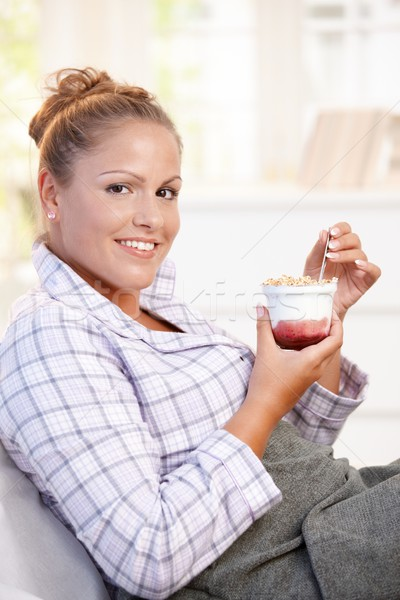 Attractive young woman eating yoghurt in bed Stock photo © nyul