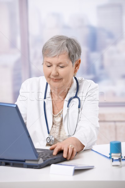 Stock photo: Senior doctor using laptop computer