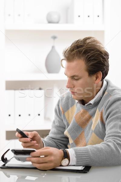 Stock fotó: Fiatalember · telefon · gépel · mobiltelefon · otthon · férfi