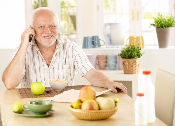 Healthy pensioner using cellphone at breakfast Stock photo © nyul