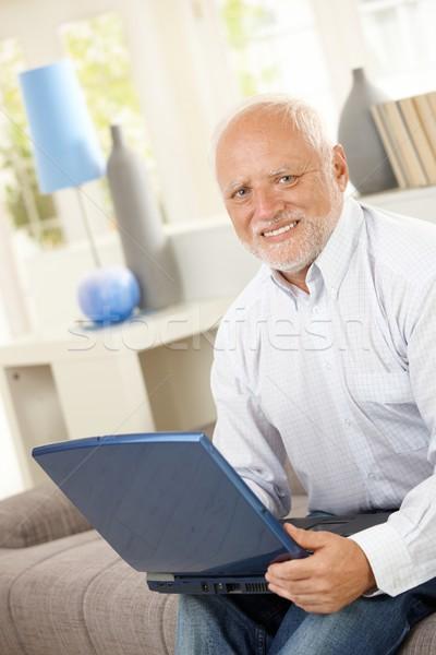 Senior met behulp van laptop computer sofa man naar Stockfoto © nyul